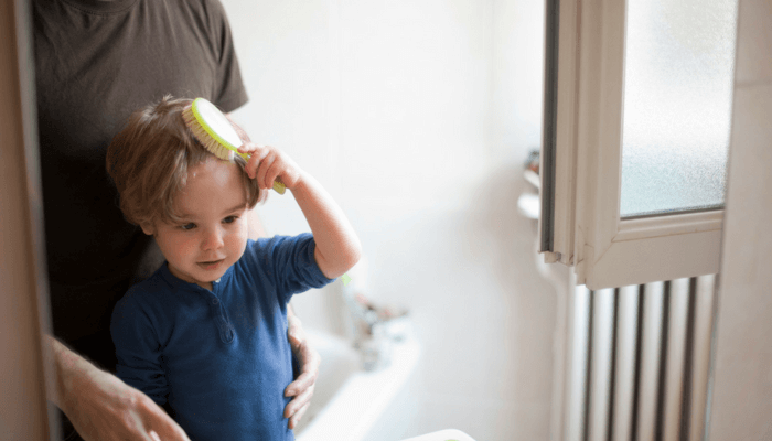 Child brushing their hair in the mirror
