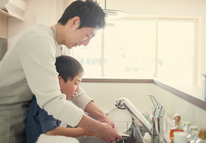 father and young son washing dishes