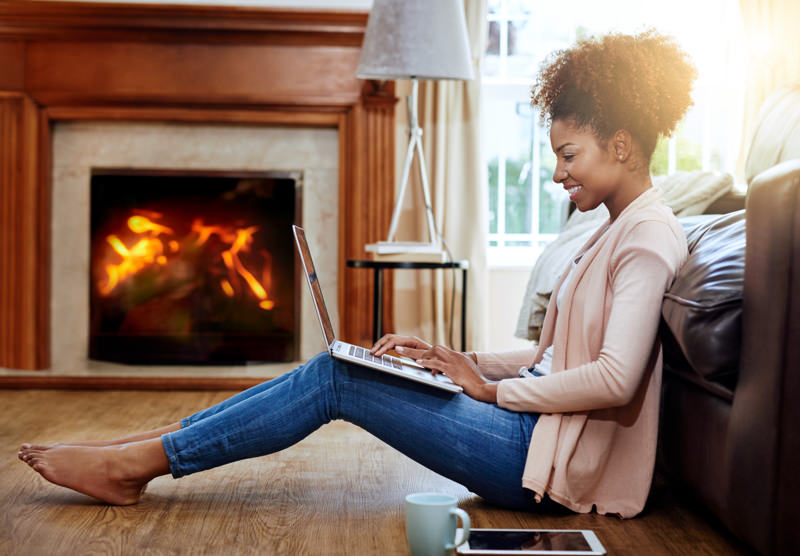 woman on laptop by the fire